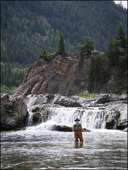 angler-choosing-fly-below-waterfall.jpg